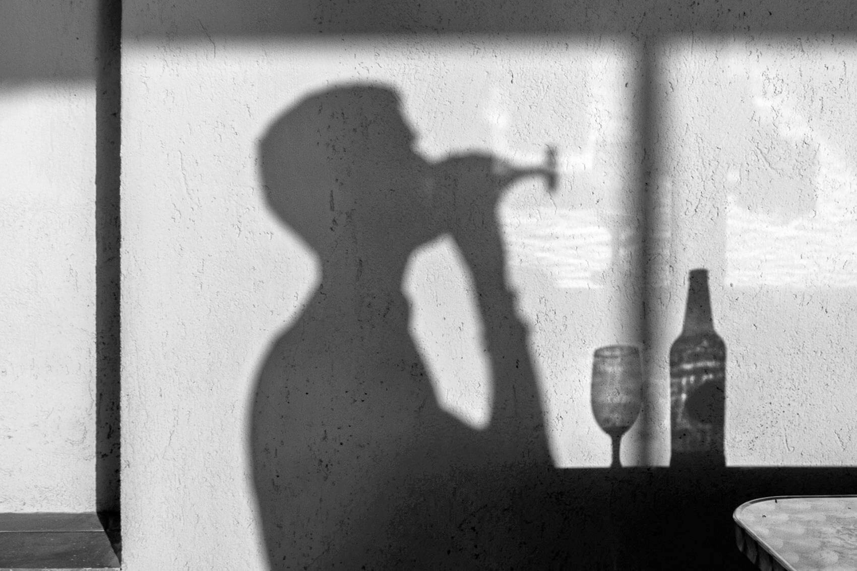 Man drinking beer and his shadow on the wall