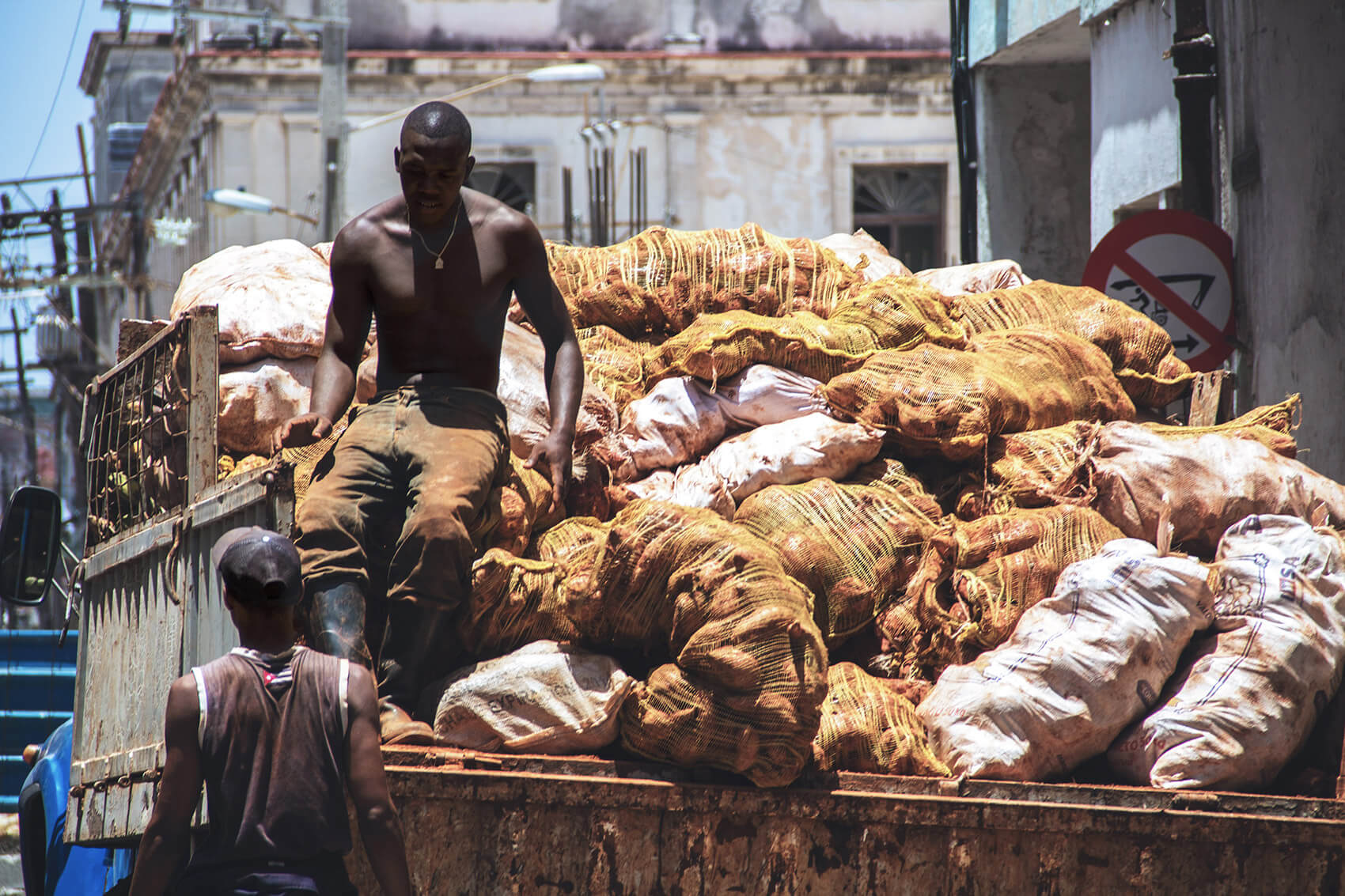 Workers unloading a truck full of potatoes.