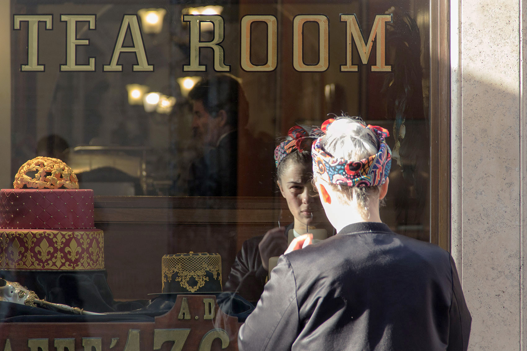 A girl mirrored in the Caffè Greco window