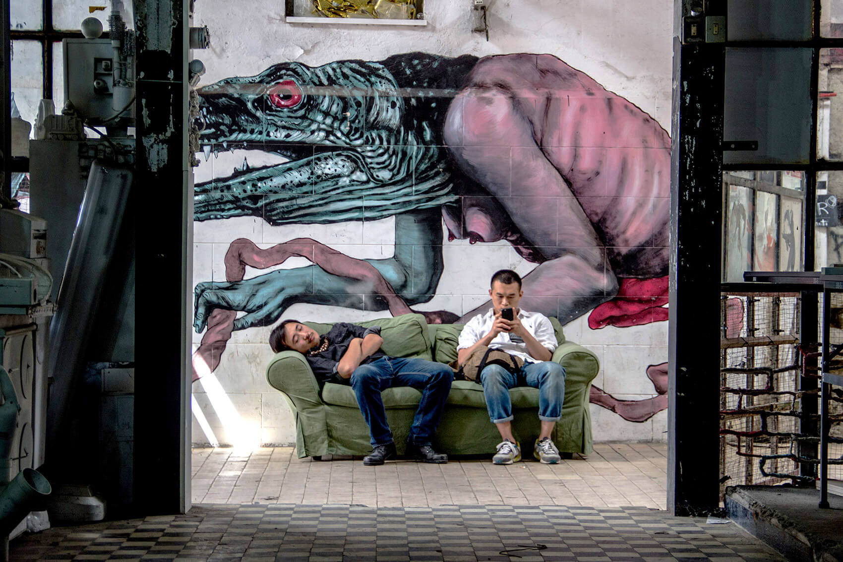 Two relaxed guys with graffiti monster creeping in the back.