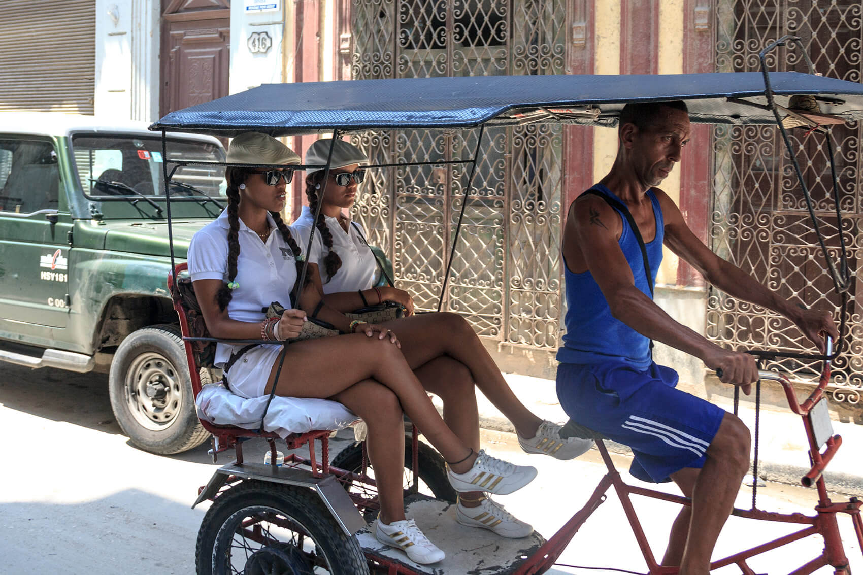 Two twin girls on a cycle taxi in Havana.